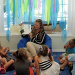 Education curator reading a storybook to a group of children