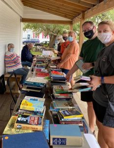 volunteers at table filled with books being sold
